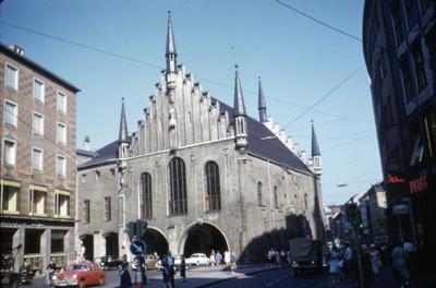 Personas caminan al exterior de edificio de estilo gotico