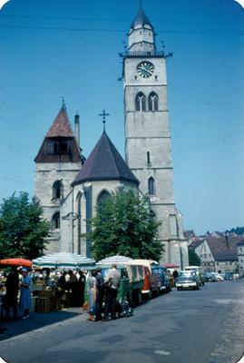 Gente en puestos ambulantes frente a una iglesia de