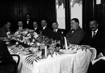 Tomas Sansano, empresario español sentado a la mesa con varios hombres, durante un banquete en un salón, retrato de grupo