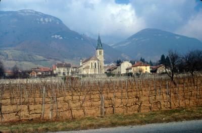 Poblado y su iglesia bajo el macizo montañoso de los Alpes