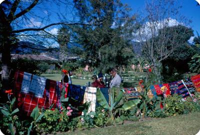 Turistas observan un tendedero de artesanias textiles en un jardin