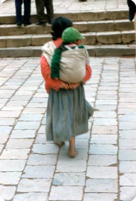 Mujer con su hijo a cuestas en la espalda