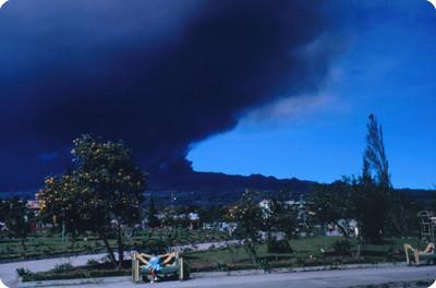 Niña sentada en banca de un parque, al fondo fumarola del volcan Poas