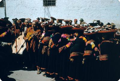 Indígenas y musicos en una calle, durante festividad popular
