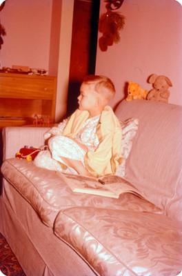 Niño con juguetes sentado sobre un sillon, retrato