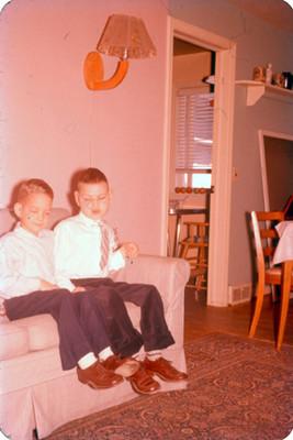 Niños sentados en el sillon de una sala, retrato