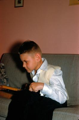 Niño sentado en el sillon de una sala, retrato