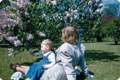 Mujer con niño sobre sus piernas sentadas en un jardin
