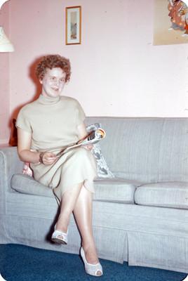 Edith lee una revista en la sala de una casa