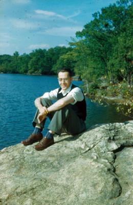 Arsen sentado sobre una roca a la orilla de un lago, retrato
