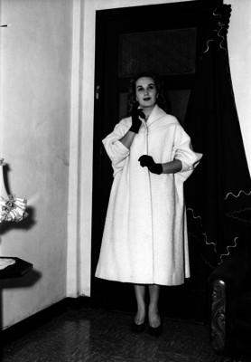 Aurora Segura parada junto a una puerta en una sala, actriz, retrato