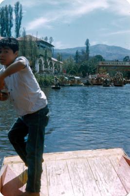 Niño en trajinera frente al embarcadero en Xochimilco