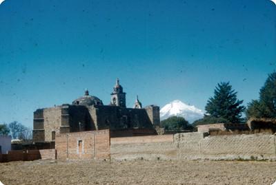 NH Mexico VillageNH, vista posterior de una iglesia, al fondo el volcan