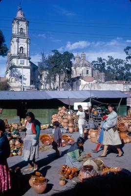 Gente en dia de tinaguis, al fondo cupula y campanario de la iglesia del poblado
