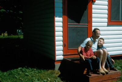 Hombre sentado con niños al exterior de su casa