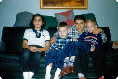 Hombre sentado en sillon con tres niños