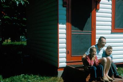 Hombre abraza a sus hijos mientras estan sentados en el exterior de su casa