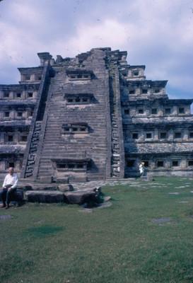 Hombre sentado frente a la fachada de la piramide de los nichos,