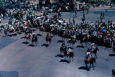 Vista lateral de contingente de charros que desfila por calles de la ciudad