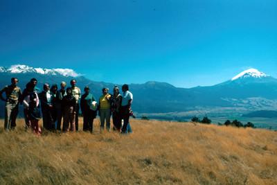 Grupo de personas sobre colina con los volcanes Iztaccihuatl y Popocatepetl de fondo