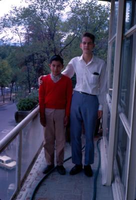 Joven abraza a niño en un balcon de hotel