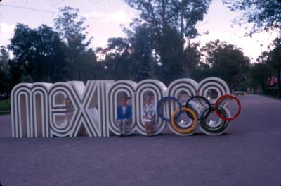 Personas sentadas en letrero de las Olimpiadas