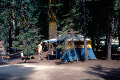 Hombre junto a casa de campaña en un bosque