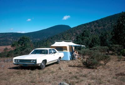 Hombre junto a una casa de campaña en la falda de un cerro