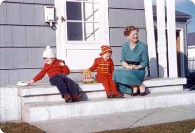 Edith Sophie e hijos sentados frente a la puerta de entrada a su casa