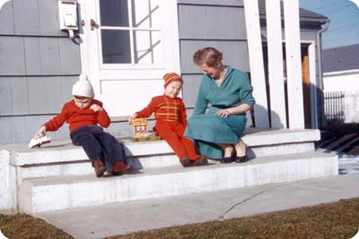 Edith Sophie e hijos sentados en las escaleras de entrada de su casa