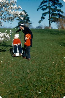 Edith Sophie y sus hijos observan un arbol de flores blancas en un parque