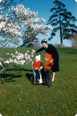 Edith Sophie y sus hijos junto a un arbol de flores blancas en un parque