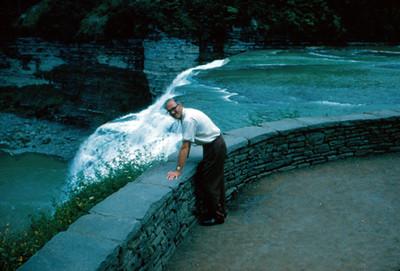 Hombre se apoya en barda de proteccion a orillas de un rio