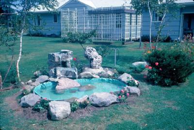 Fuente decorada con piedras en un jardin, al fondo la casa