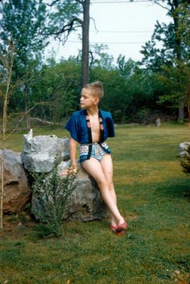 Niño de pie con traje de baño en un jardin