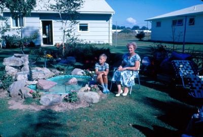 Mujer y niño sentados frente a la fuente del jardin
