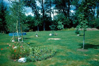 Jardin con arboles recien plantados y flores