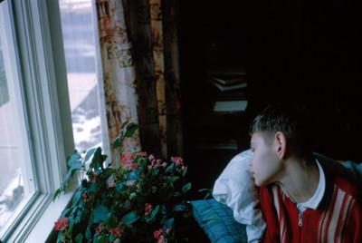 Niño duerme frente a la ventana de su cuarto