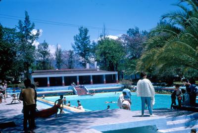 Gente en la alberca y jardines del Hotel Peñafiel