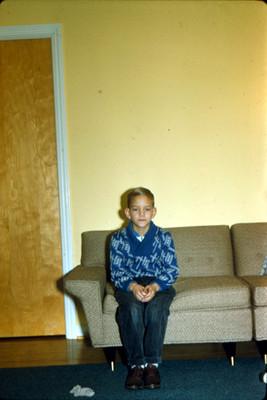 Niño sentado en sillon de una habitacion