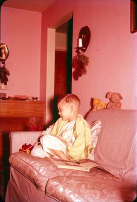 Niño con cobija y pijama, sentado en un sillon con juguetes