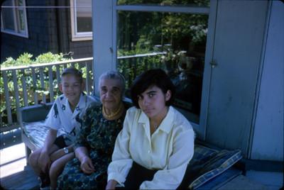 Niño y dos mujeres sentados en la terraza de una casa, en