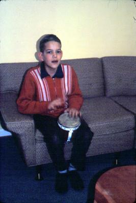Niño toca tambor sentado en un sillon