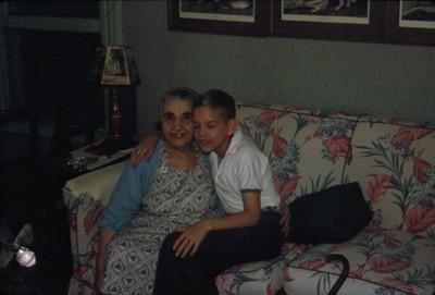 Anciana abraza a niño mientras estan sentados en sala