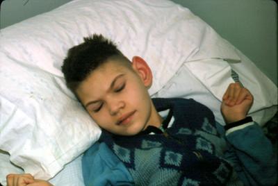 Niño duerme recostado en cama