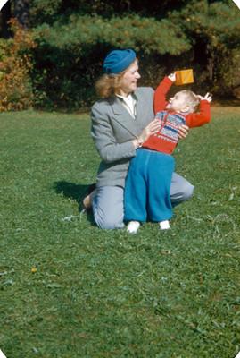Mujer juega con bebe en jardin