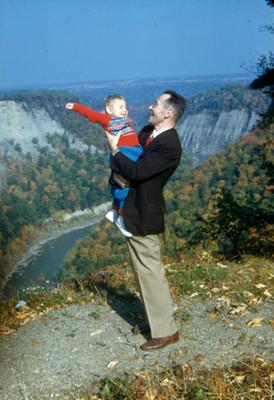 Hombre carga a niño en una colina