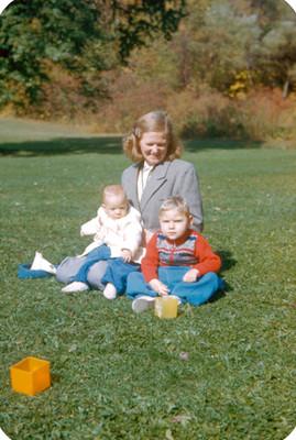 Mujer sentada con bebes en jardin