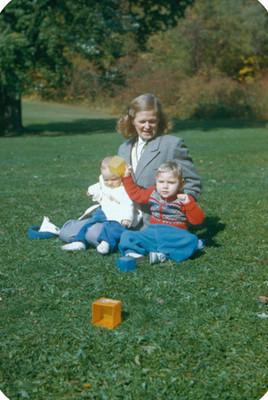 Mujer sentada con bebes en pasto