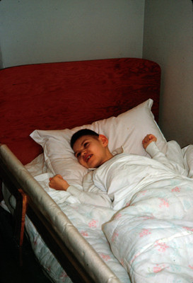 Niño con discapasidad mental recostado en una cama